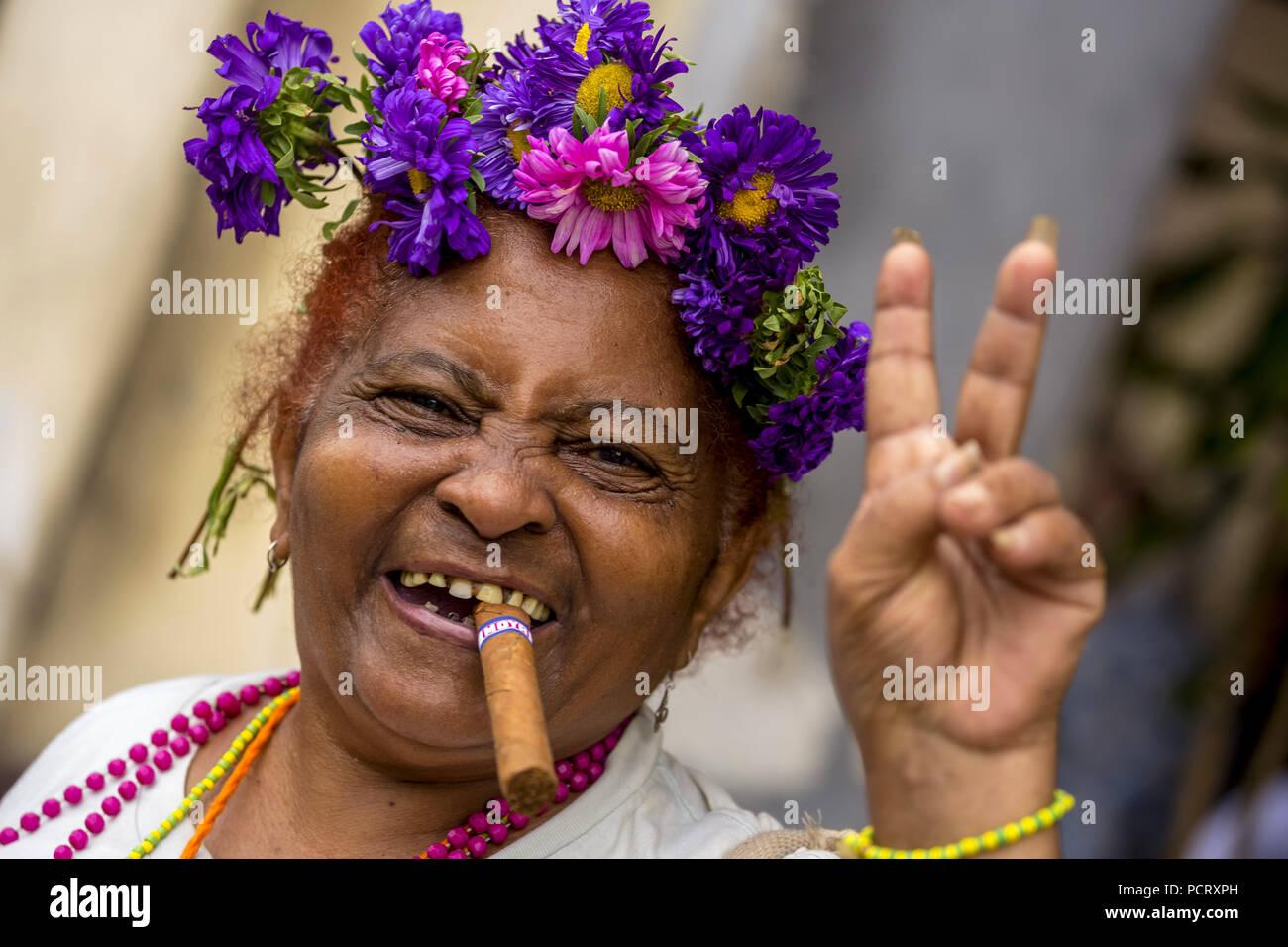 Peace sign, old Cuban woman with floral decoration and cigar posing for tourists to receive a tip, La Habana, Havana, La Habana, Cuba, Cuba - Stock Image