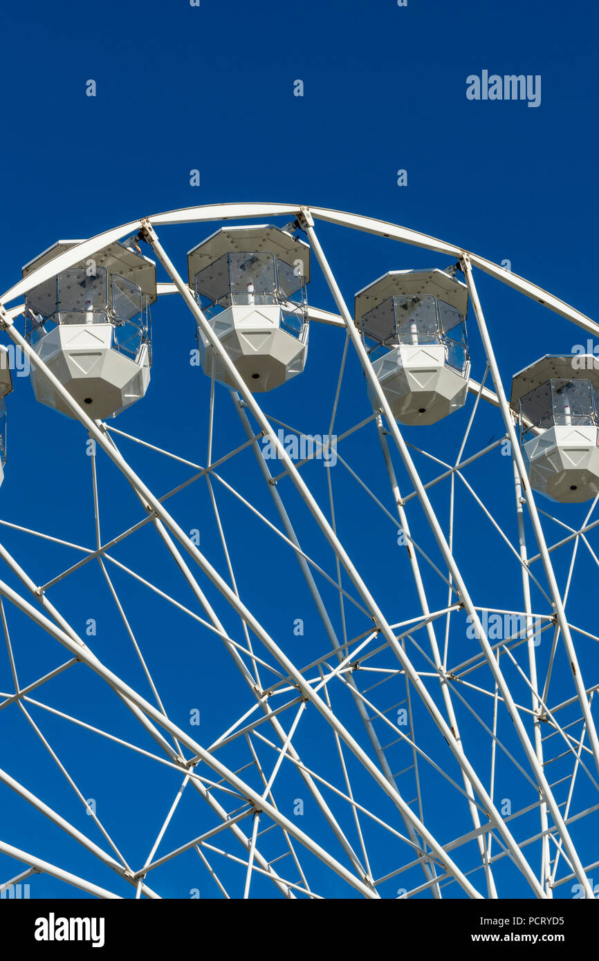 gondolas on a large white ferris wheel or big wheel at a funfair or mop fair at cowes oon the isle of wight during the annual cowes week regatta. - Stock Image