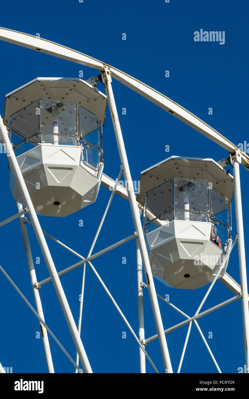 tow gondolas on a large white ferris wheel or big wheel at a fairground. fairground rides and attractions. - Stock Image