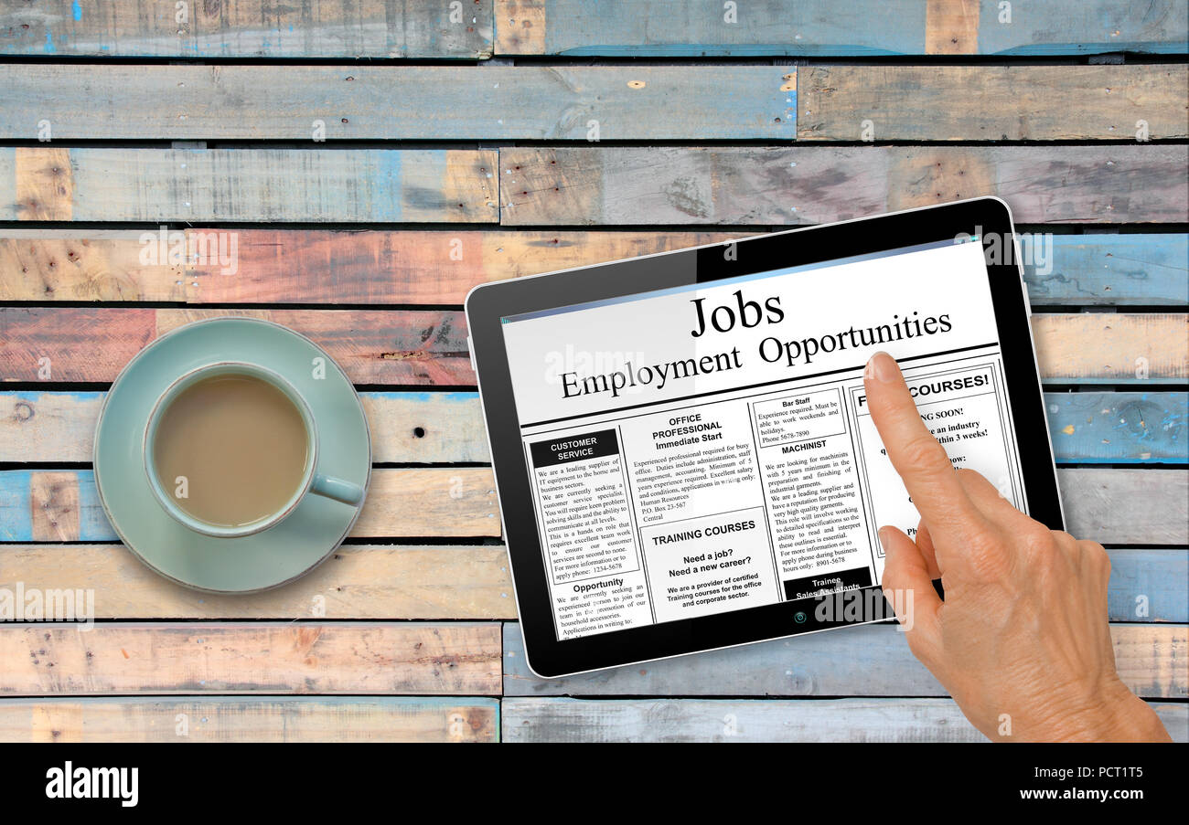 Online job hunting Hand with computer tablet reading employment ads on table with coffee - recruitment concept - Stock Image
