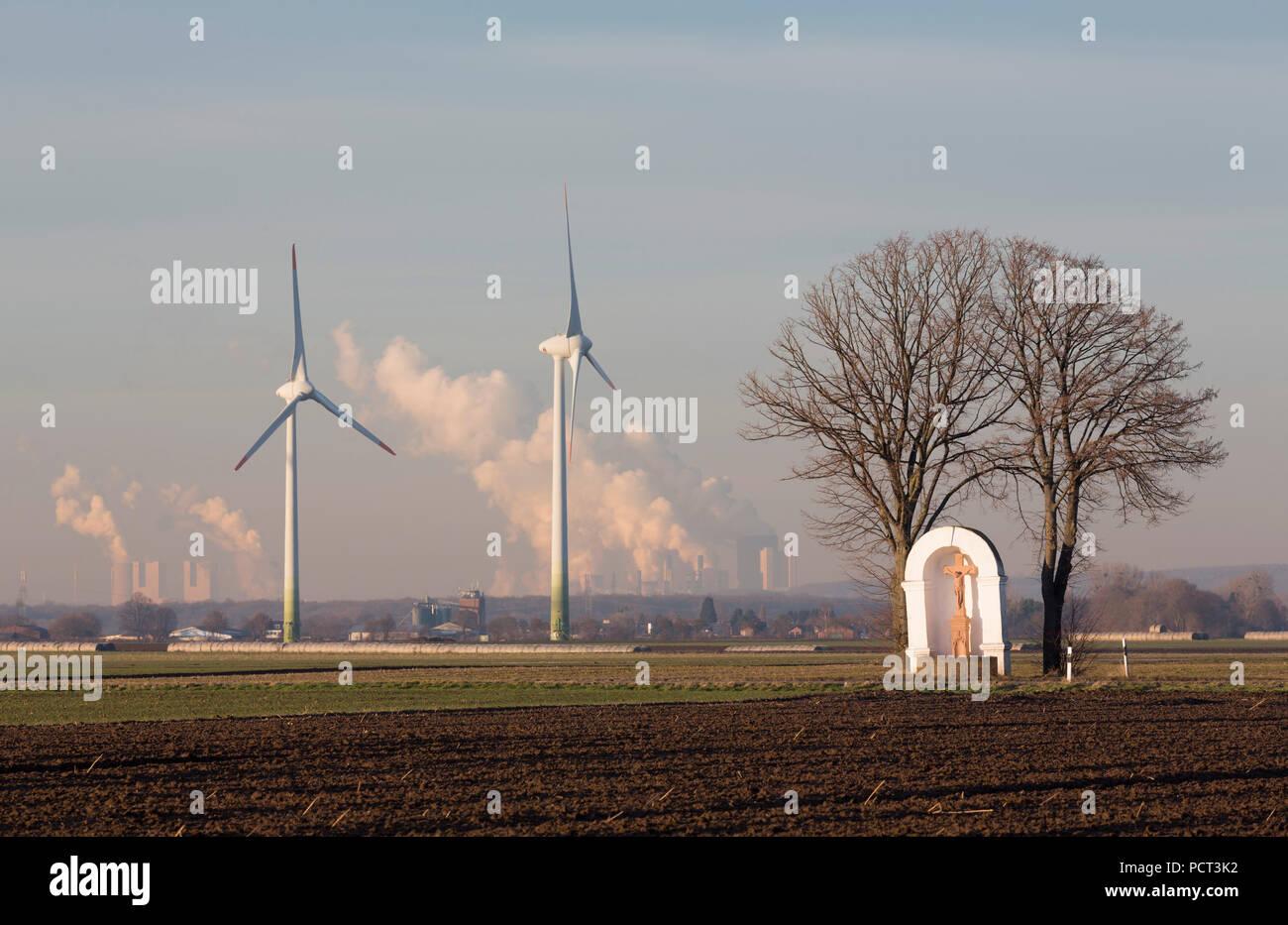 von zwei Linden flankierter Bildstock aus dem 18. Jahrhundert, dahinter zwei Windkraftanlagen und Kohlekraftwerke (Rheinisches Braunkohlerevier) - Stock Image