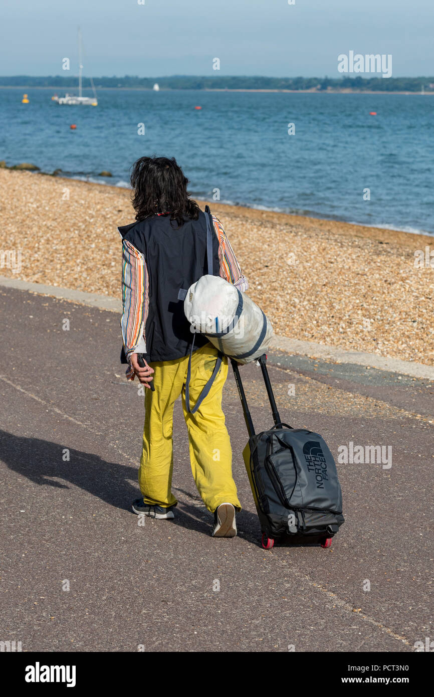 a man wearing yellow trousers and long haired walking along the sea froint at cowes on the isle of wight carrying a sailing bag and a pull along case. - Stock Image