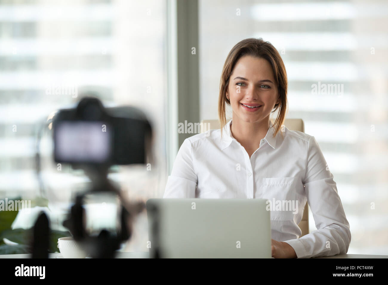 Confident businesswoman recording video course on camera - Stock Image