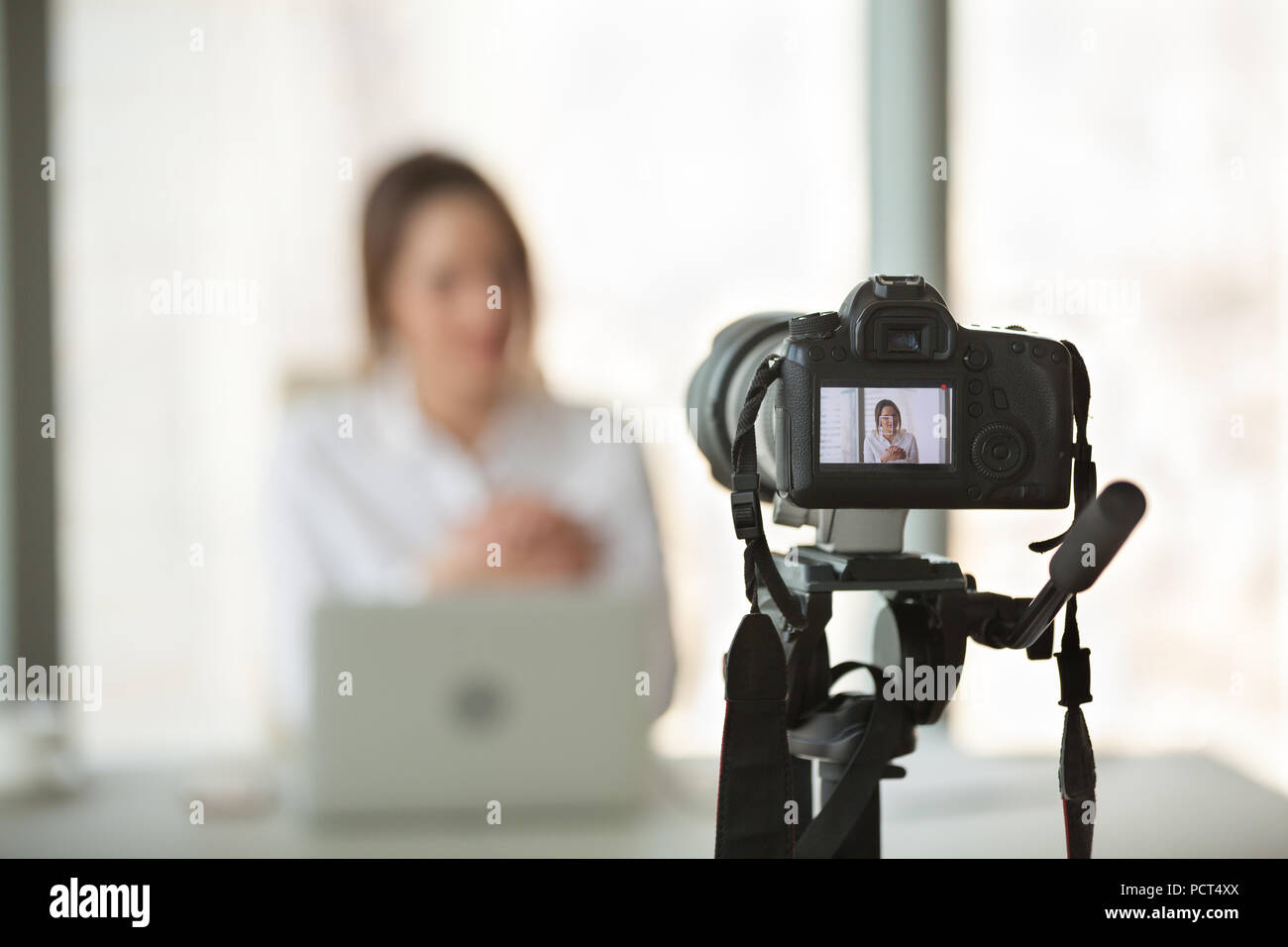 Video camera filming live training of successful business coach - Stock Image