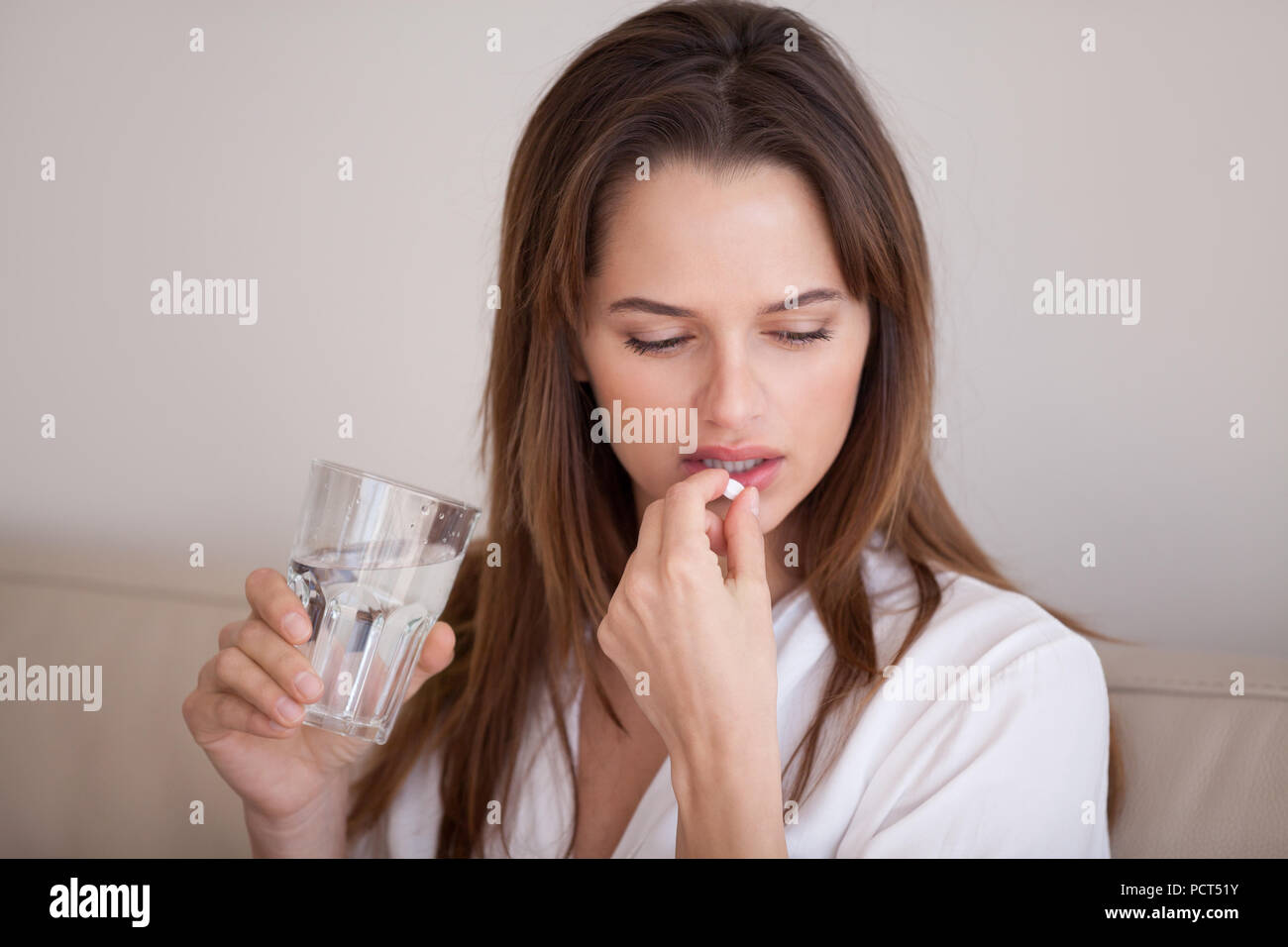 Sad millennial woman taking pill to cure pain or depression - Stock Image