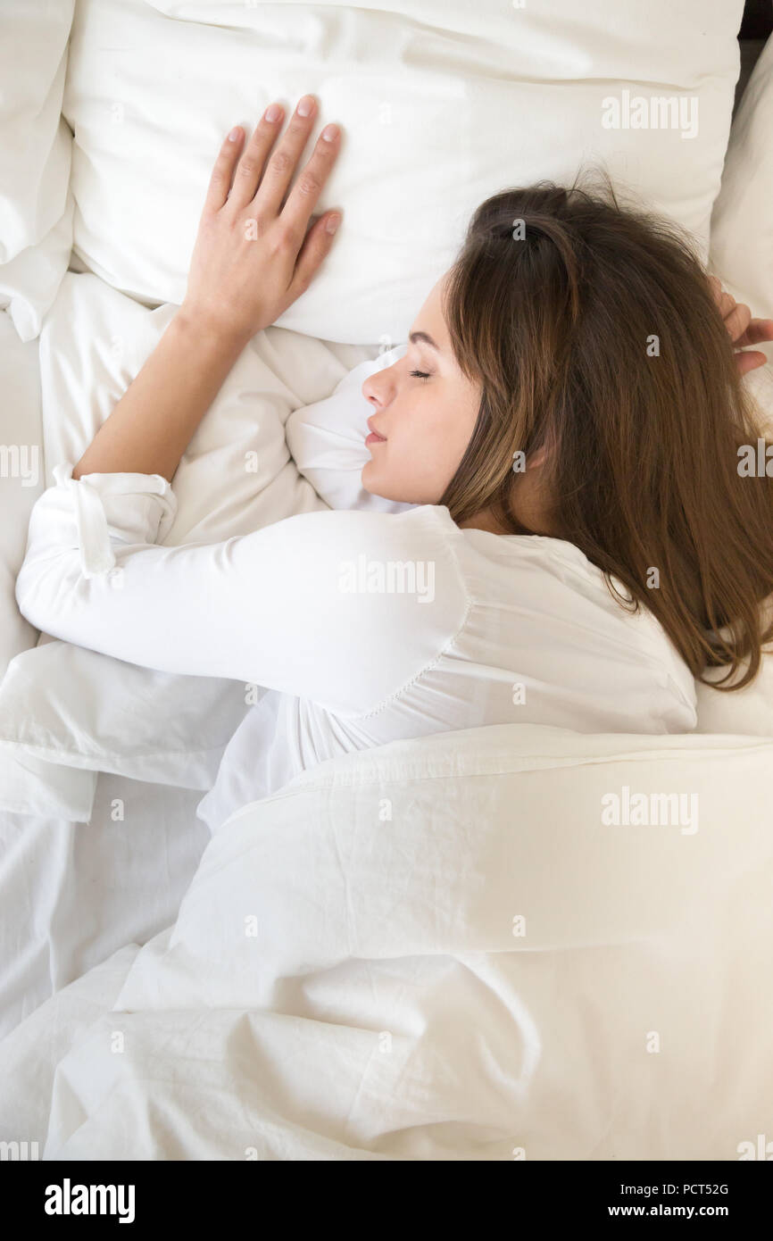 Top view of calm young female sleeping peacefully in bed - Stock Image