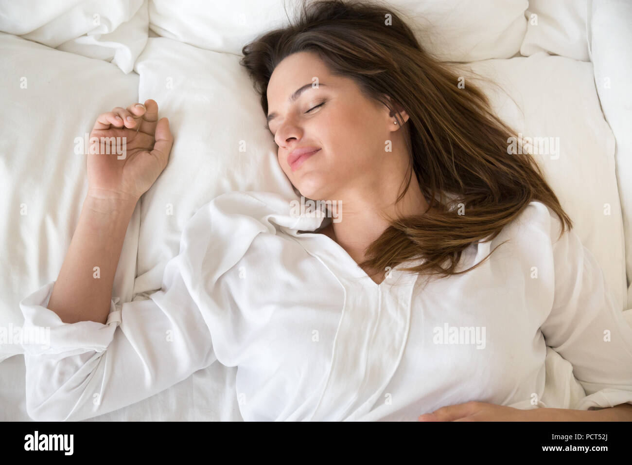 Relaxed young female sleeping well in cozy white bed - Stock Image