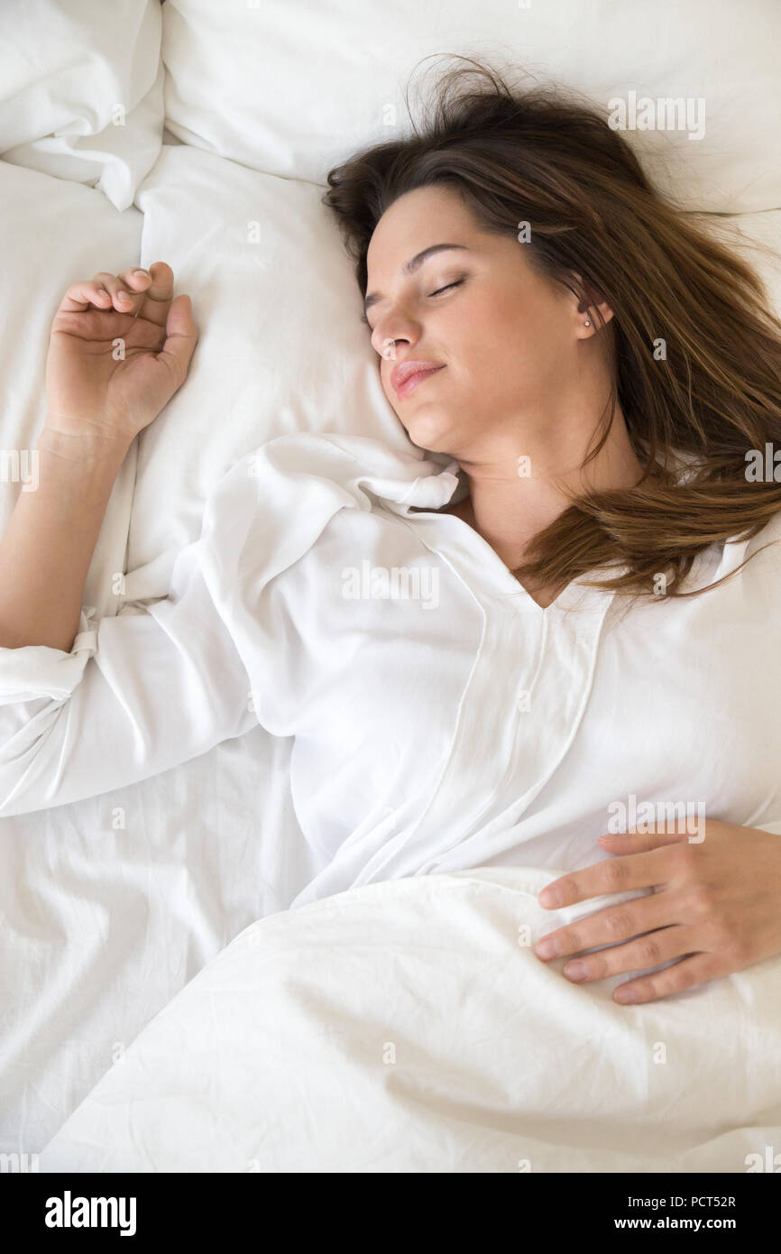 Calm girl relaxing sleeping on soft pillows in bedroom - Stock Image