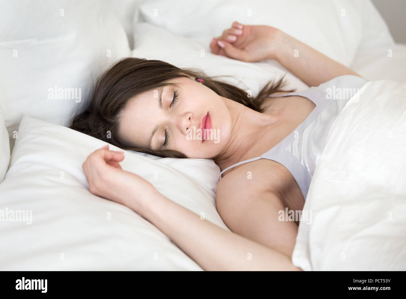 Young woman relaxing sleeping in cozy white bed - Stock Image