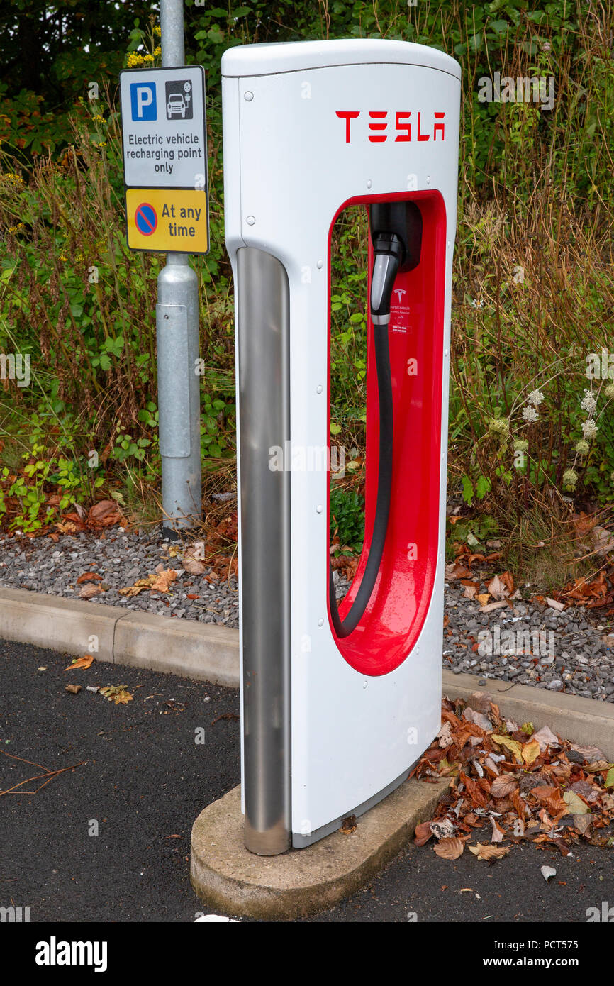 SARN, UNITED KINGDOM - AUGUST 2, 2018 : A  Tesla Supercharger and parking sign at the Sarn Park motorway services off the M4 near Bridgend in Wales. - Stock Image