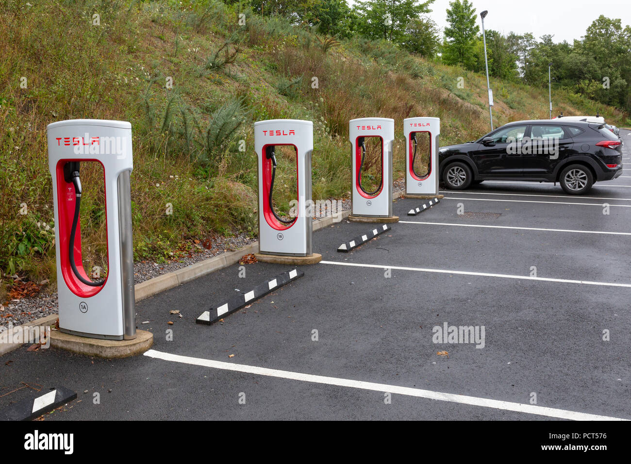 SARN, UNITED KINGDOM - AUGUST 2, 2018 : A row of Tesla Superchargers next to empty parking bays at the Sarn Park motorway services off the M4 near Bri - Stock Image