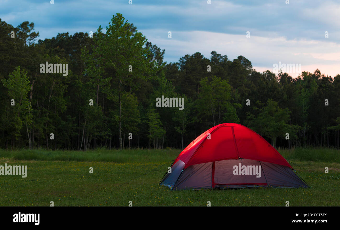 Small backpacking tent set up at a treeline as the sun is setting on a cloudy day & Small backpacking tent set up at a treeline as the sun is setting on ...