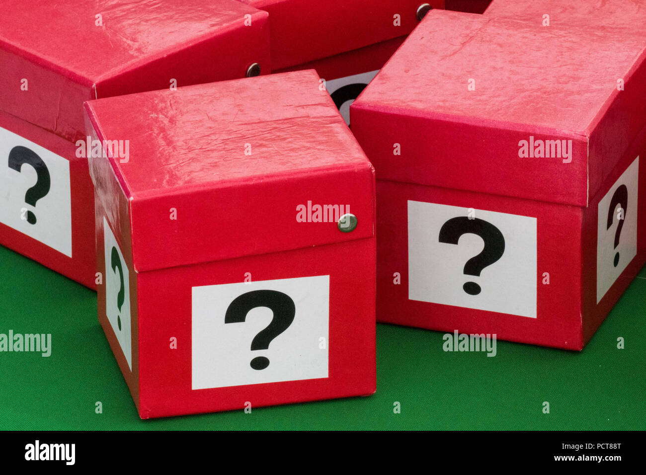 a number of red boxes painted with a question mark on each side. guessing what is in the secret box. lottery and gambling. - Stock Image