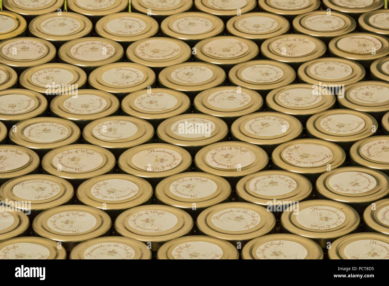 large number of jam jar lids made from metal forming a pattern. storage jars stacked on a shelf making lines and rows packaged ready for distribution - Stock Image