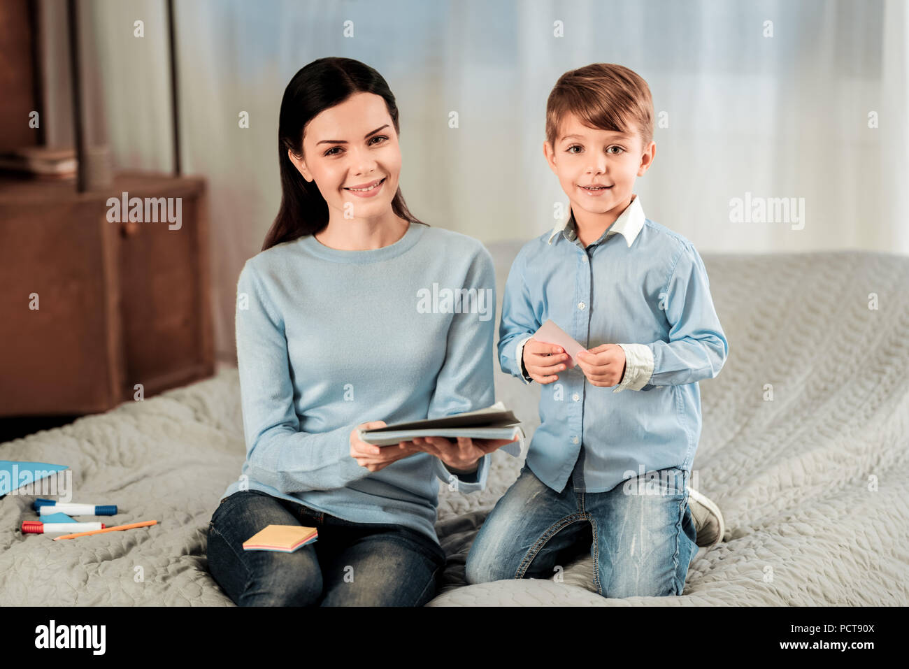 Pleasant positive mother and son looking at you - Stock Image