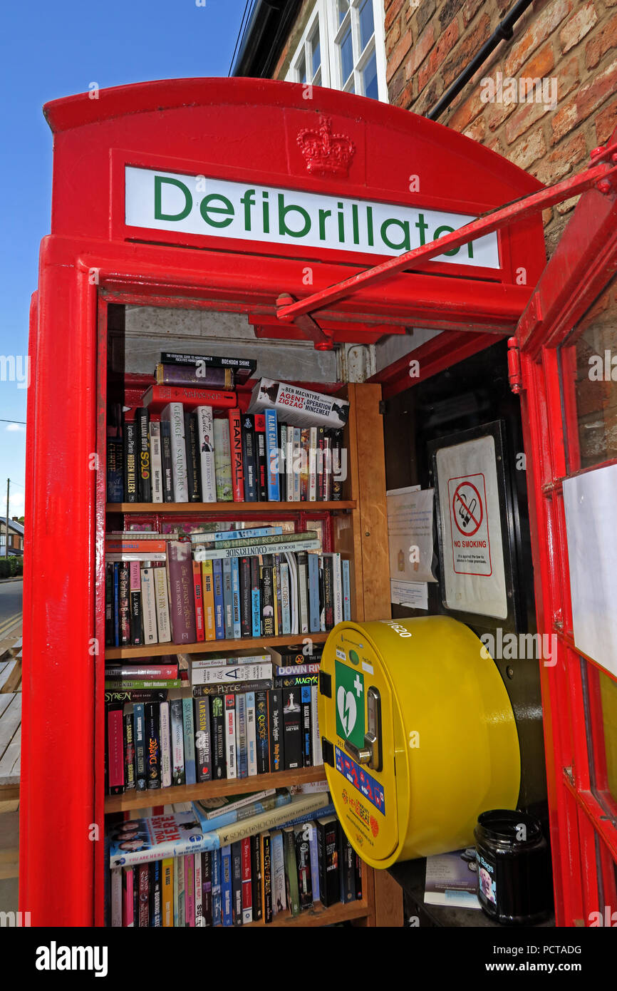 Hatton village K6 red telephone box, used as Defibrillator and book lending library, Hatton Lane, Warrington, Cheshire, North West England, UK, WA4 4D - Stock Image