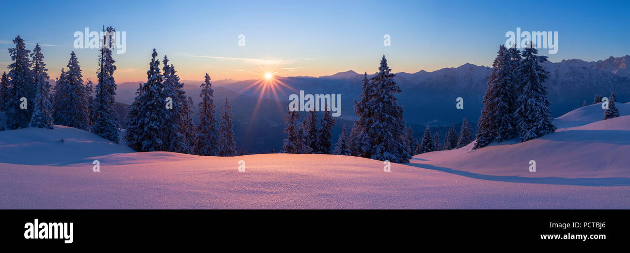 Sunrise on the Wallgau Alm with a view of the Karwendel mountains, in the foreground the powder snow glistening in the rising sun, - Stock Image