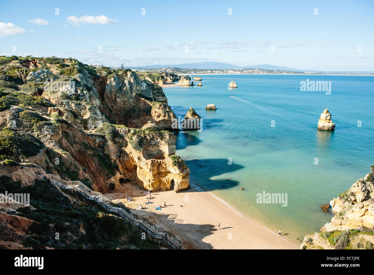 Beautiful views of the Atlantic Ocean off the coast of Portugal near the city of Lagos. People on the beach sunbathe, swim and relax during vacations or weekends or holidays - Stock Image