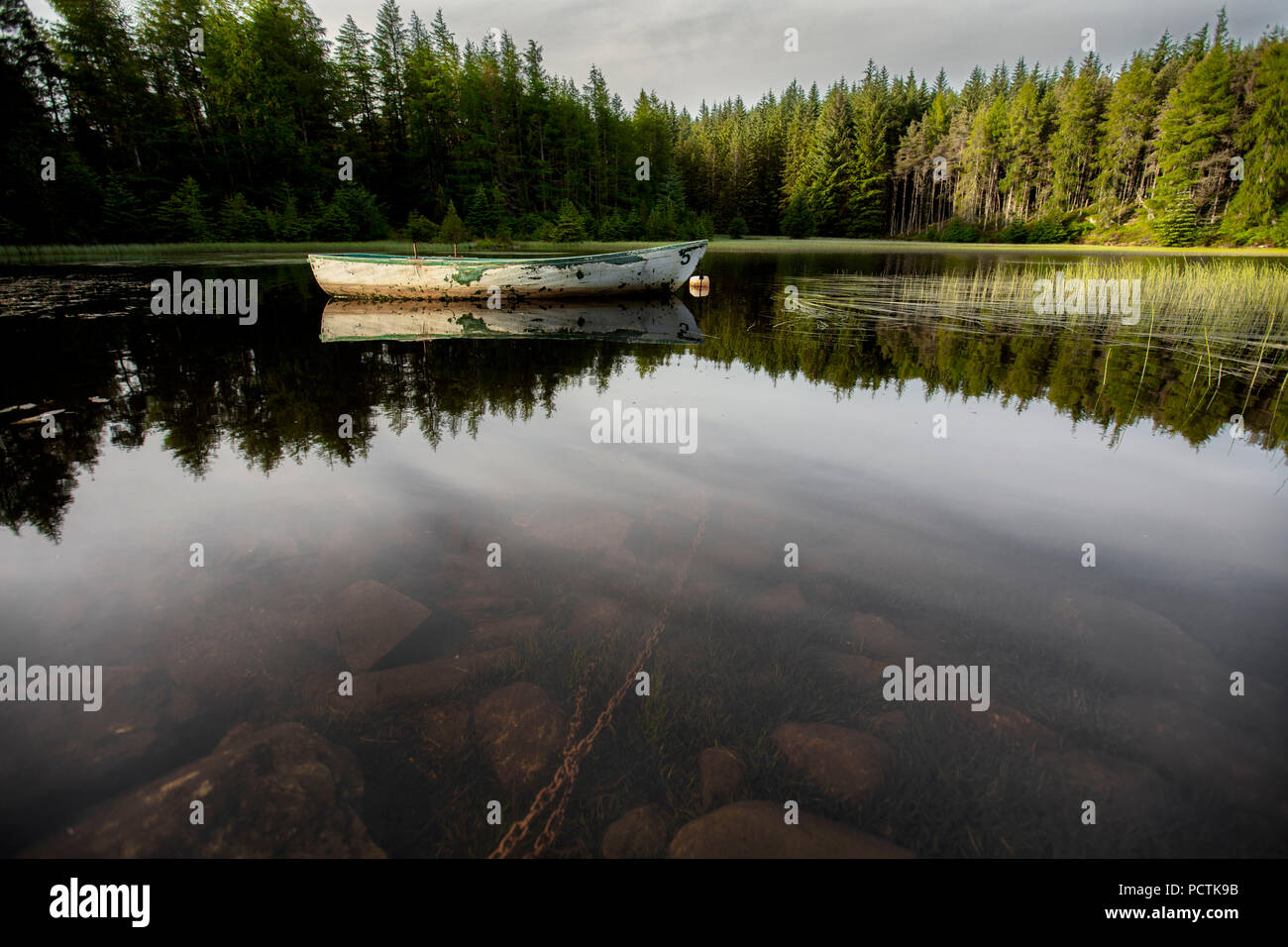 loch in scotland still water with small rowing fishing boat - Stock Image