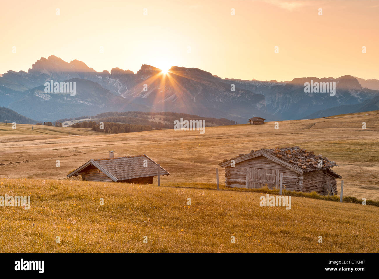 Europe, Italy, Bolzano, South Tyrol, Alpe di Siusi - Seiser Alm, Dolomites, the sun rises behind the Sassolungo Langkofel, in the foreground some wooden huts - Stock Image