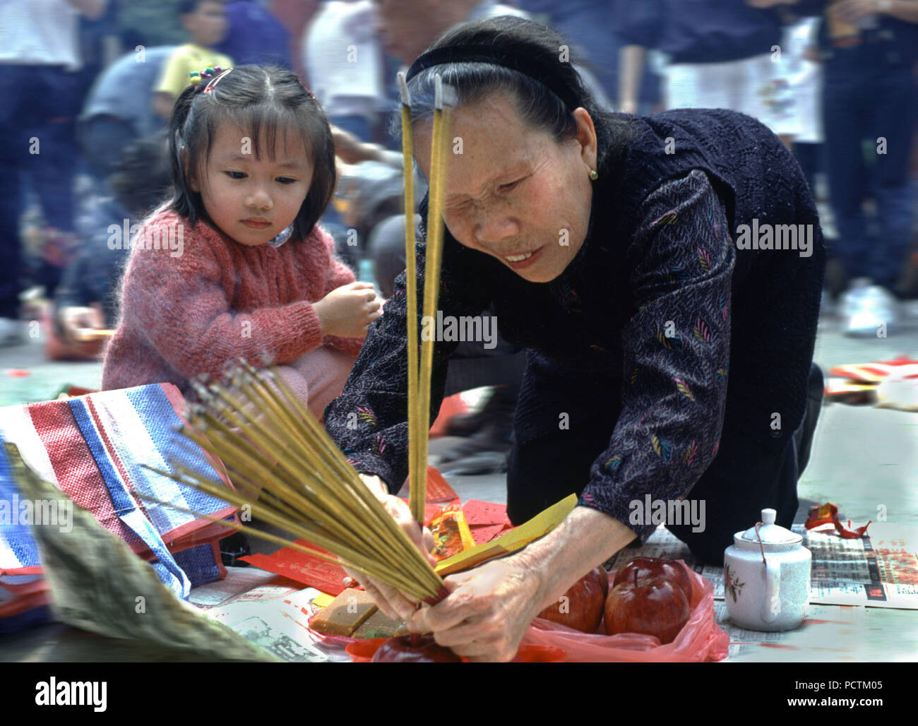 Woman and child doing rituals in Won tai Sin temple, Hongkong, China, Asia - Stock Image
