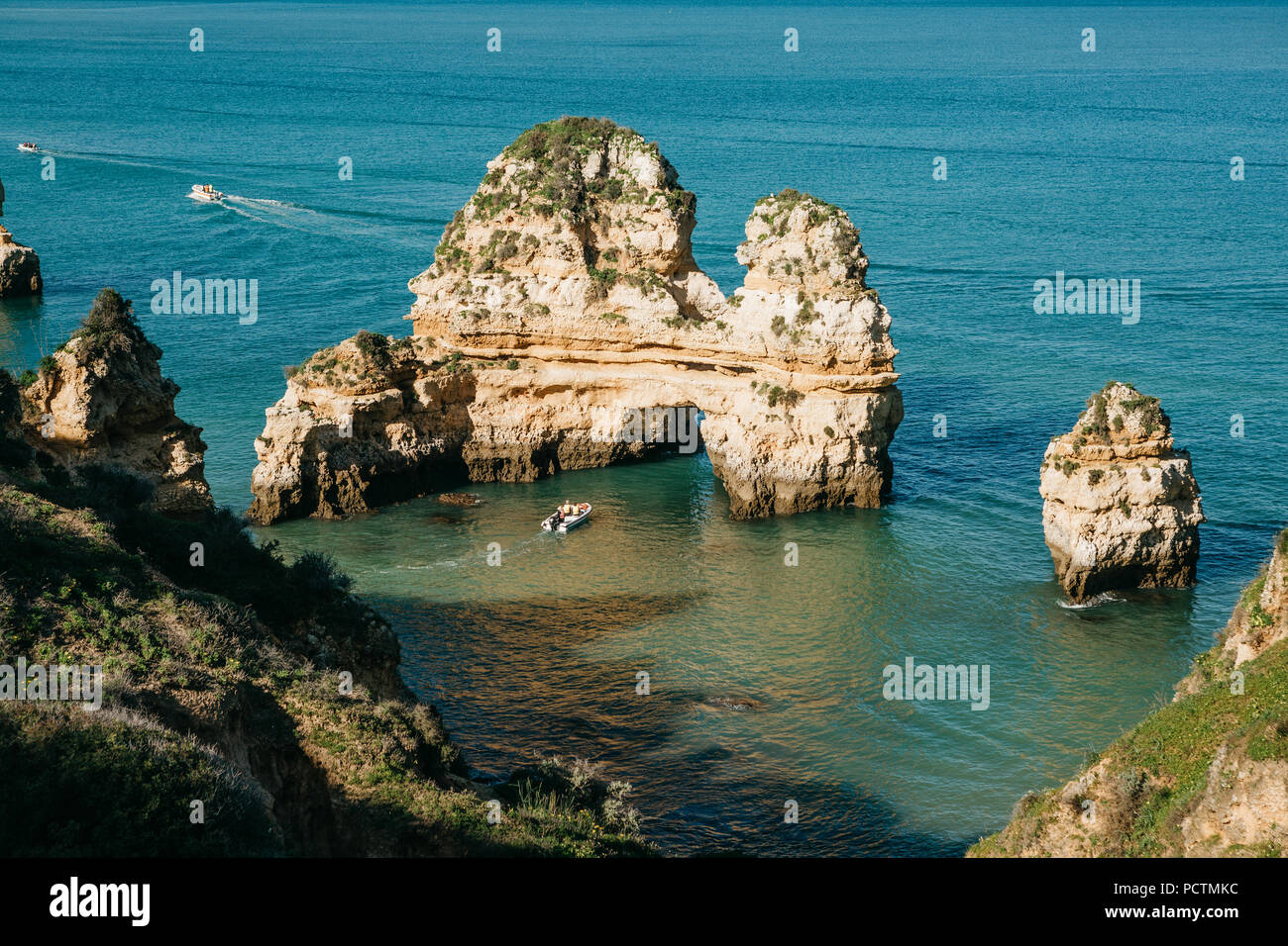 Beautiful views of the Atlantic Ocean off the coast of Portugal near the city of Lagos. A sea boat sails along the blue or turquoise water. - Stock Image
