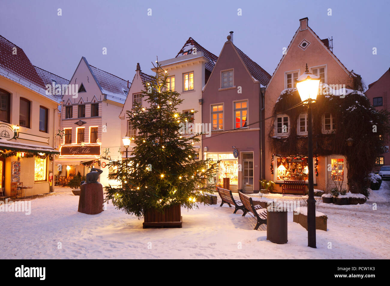 Old houses with snow and christmas lights on the stavendamm with