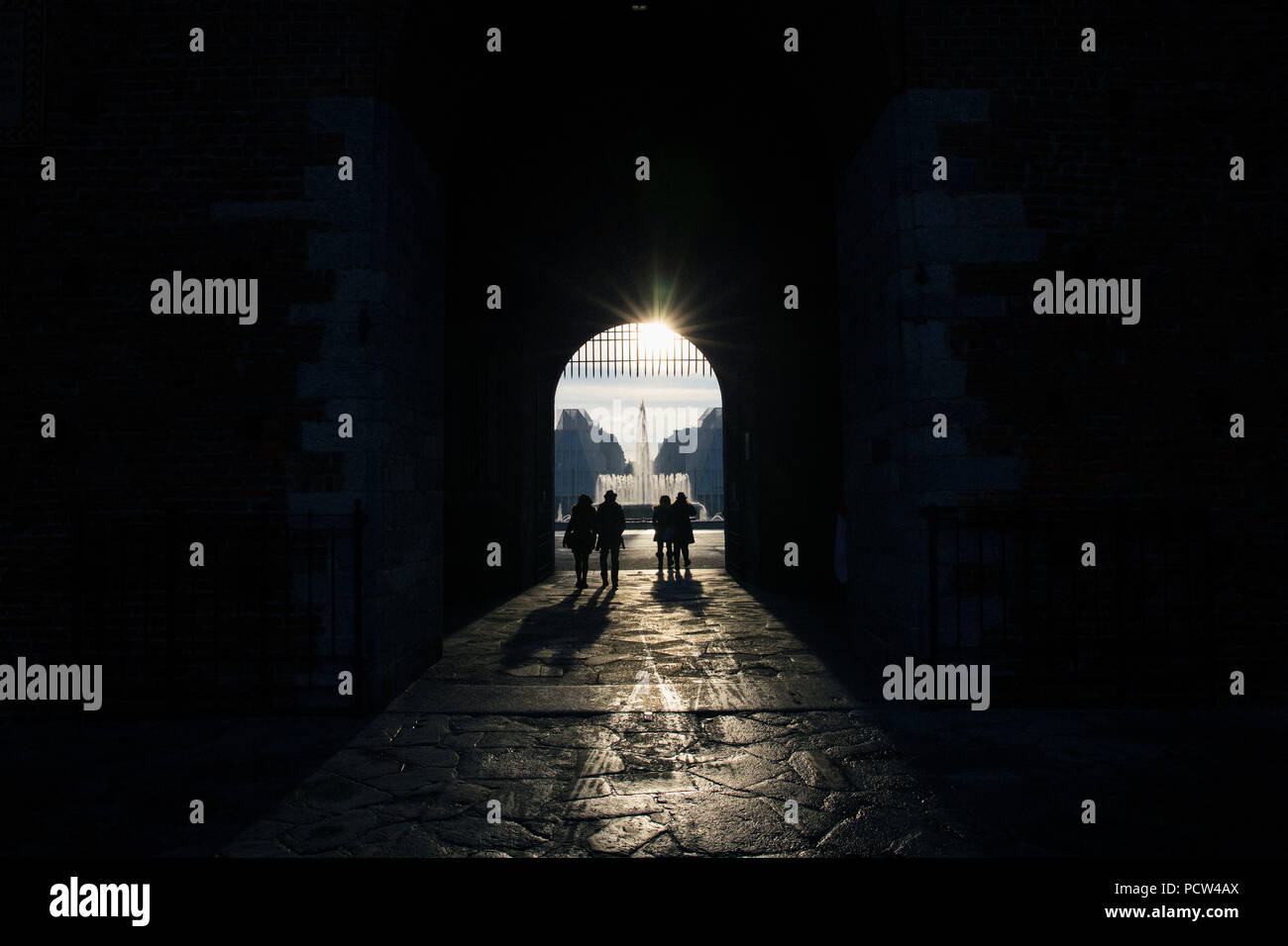 People in a dark passageway, Milan Street Photography, Italy - Stock Image