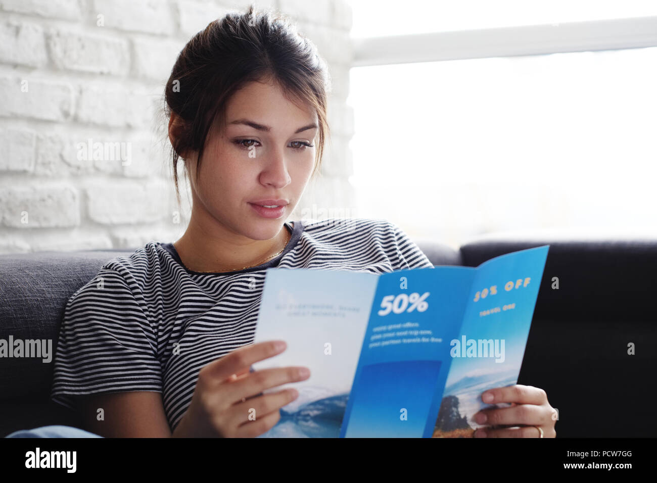 Young hispanic woman laying on couch at home, holding a travel flyer and planning next trip. Copy space on window. - Stock Image