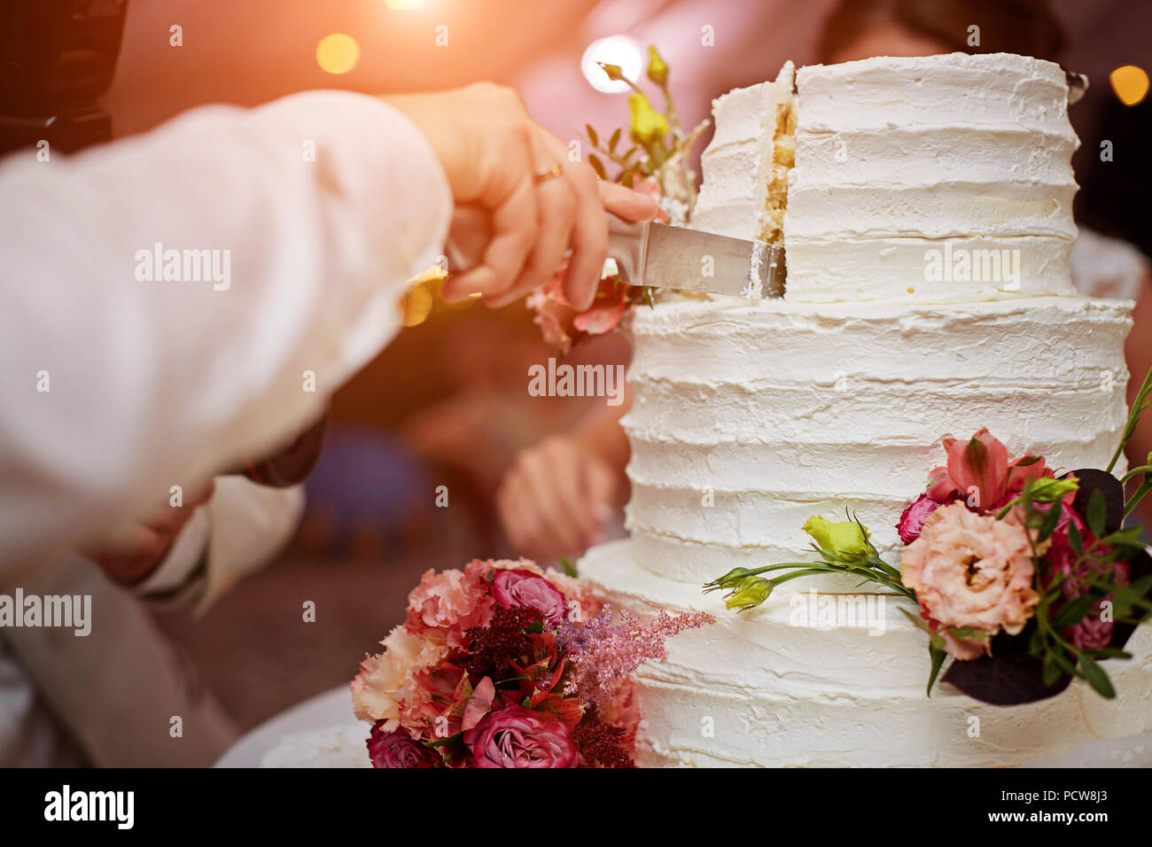Bride and groom are cutting wedding cake - Stock Image