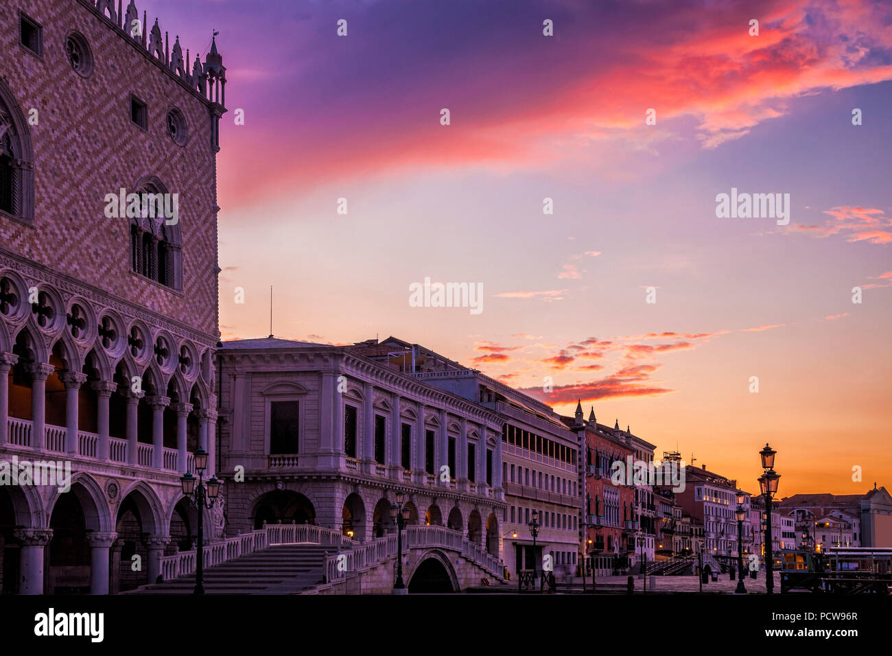 Venice's Doges Palace under vibrant clouds at sunset - Stock Image