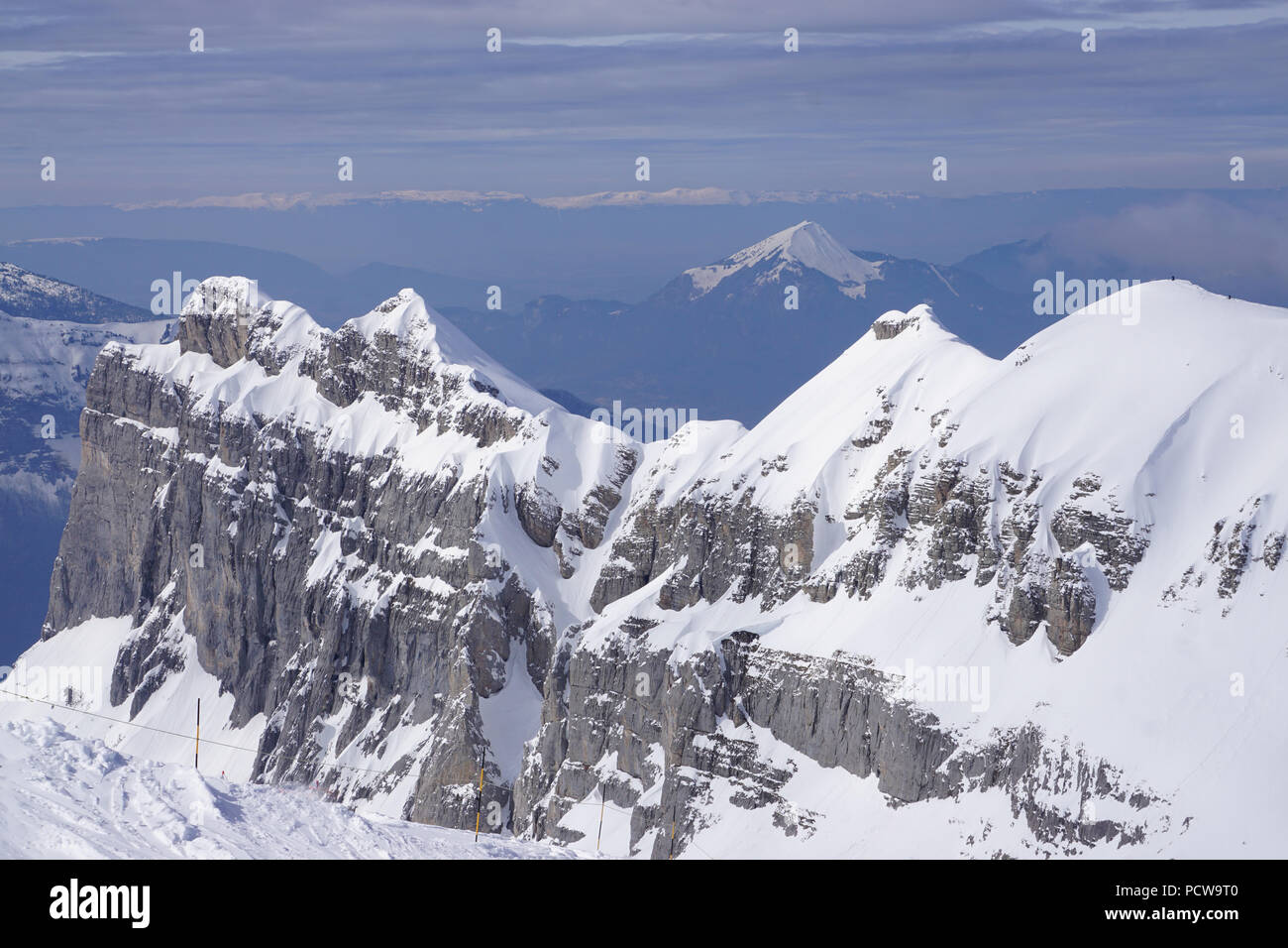 Bird eye view of the rocky snowy outcrop on a perfect clear skiing day in the Alps, France and the valley below with other mountain ranges - Stock Image