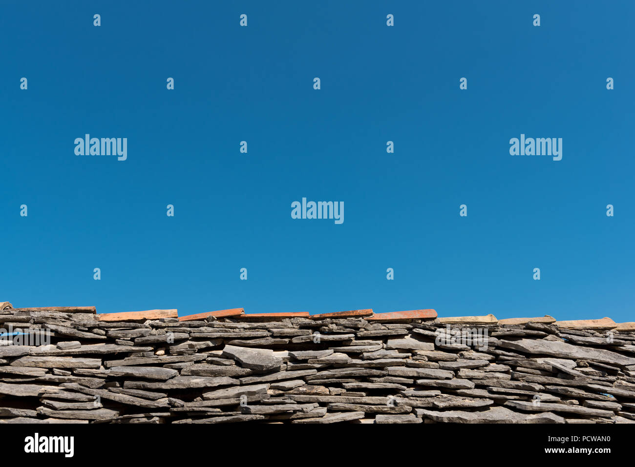 Old roof with grey stone tiles and clear blue sky in background - Stock Image