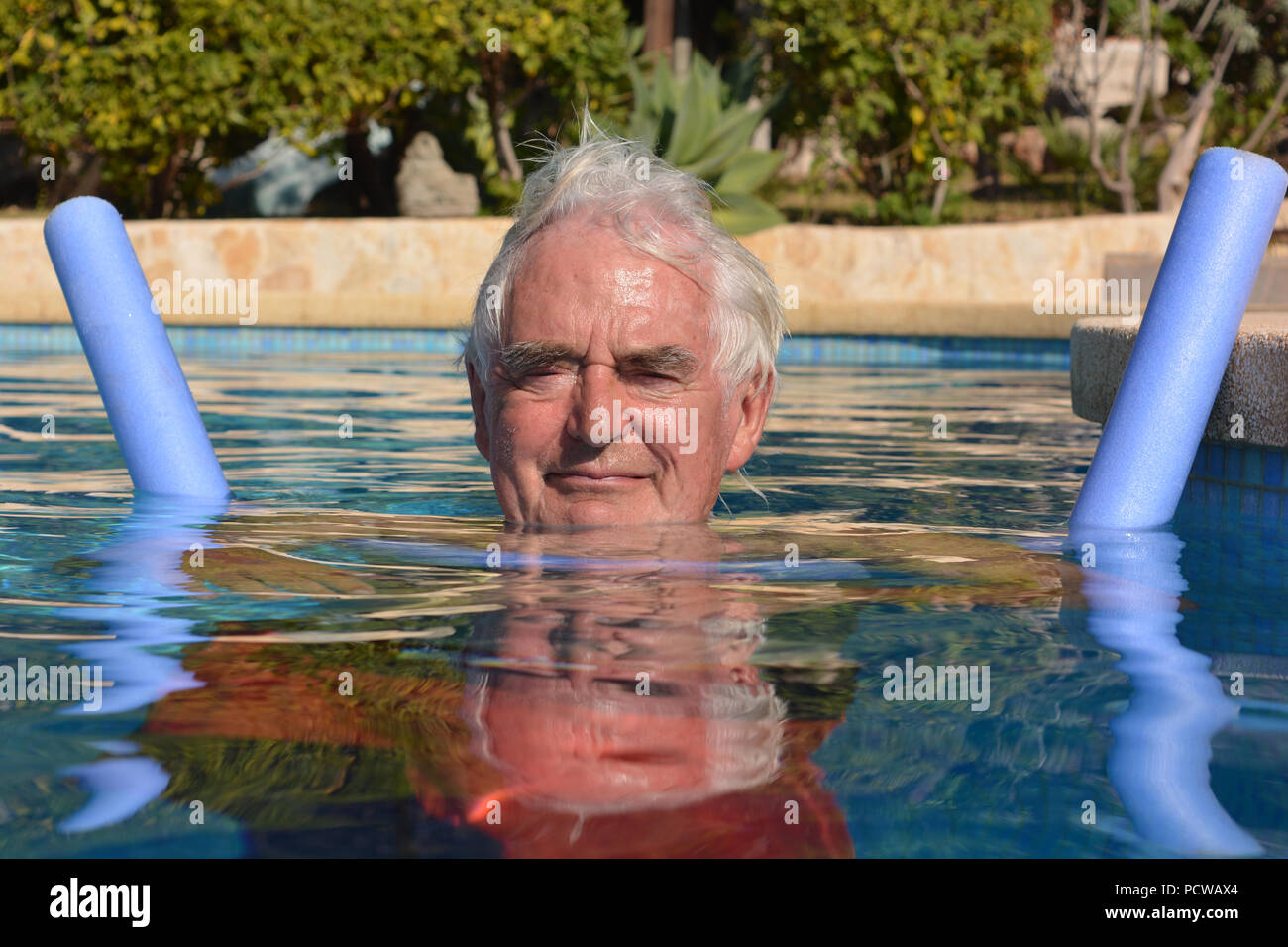 Senior man floating on a pool noodle in a swimming pool, portrait. looking at camera - Stock Image
