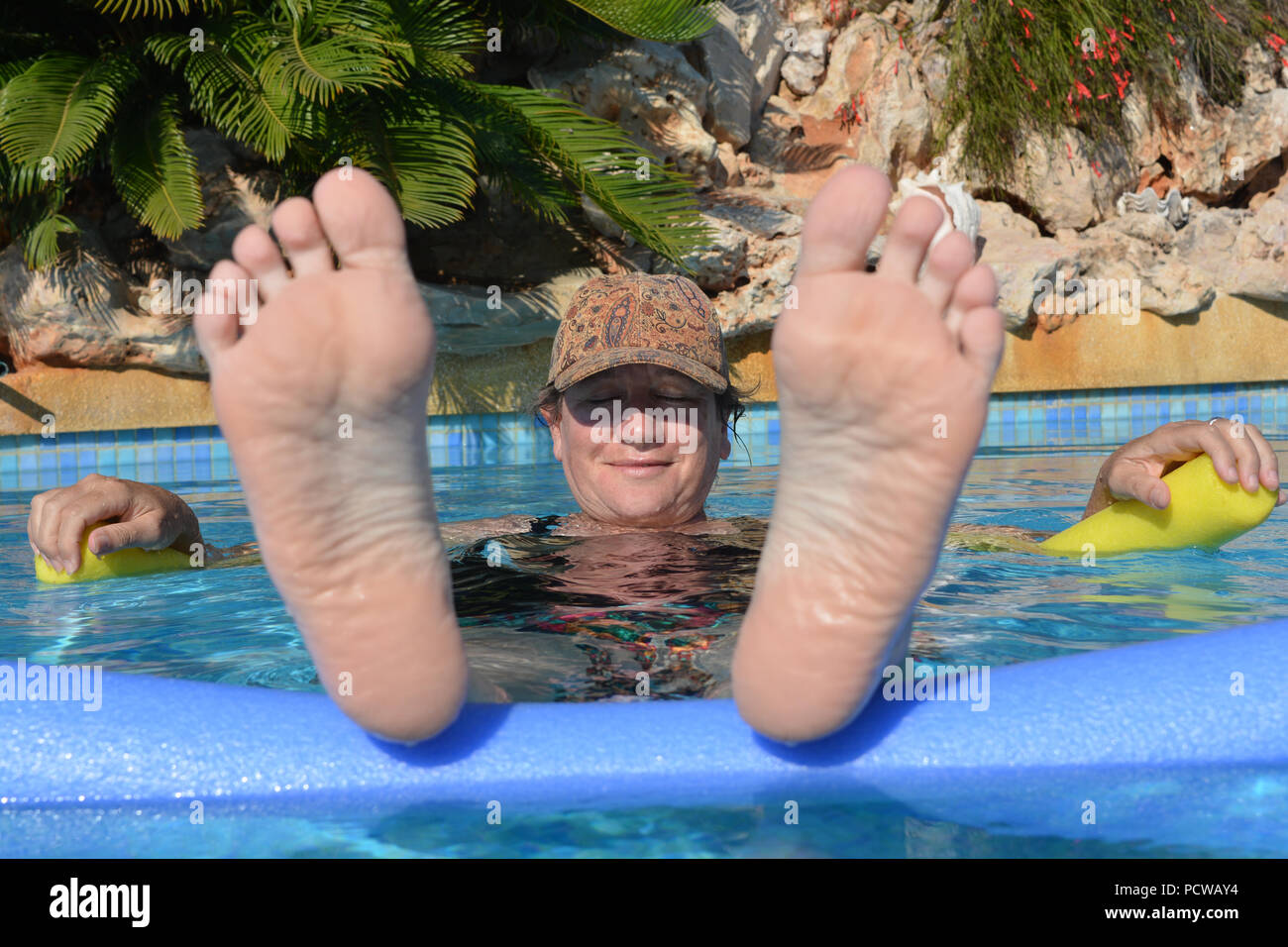 Woman using pool noodles to float in a swimming pool with her feet up - Stock Image