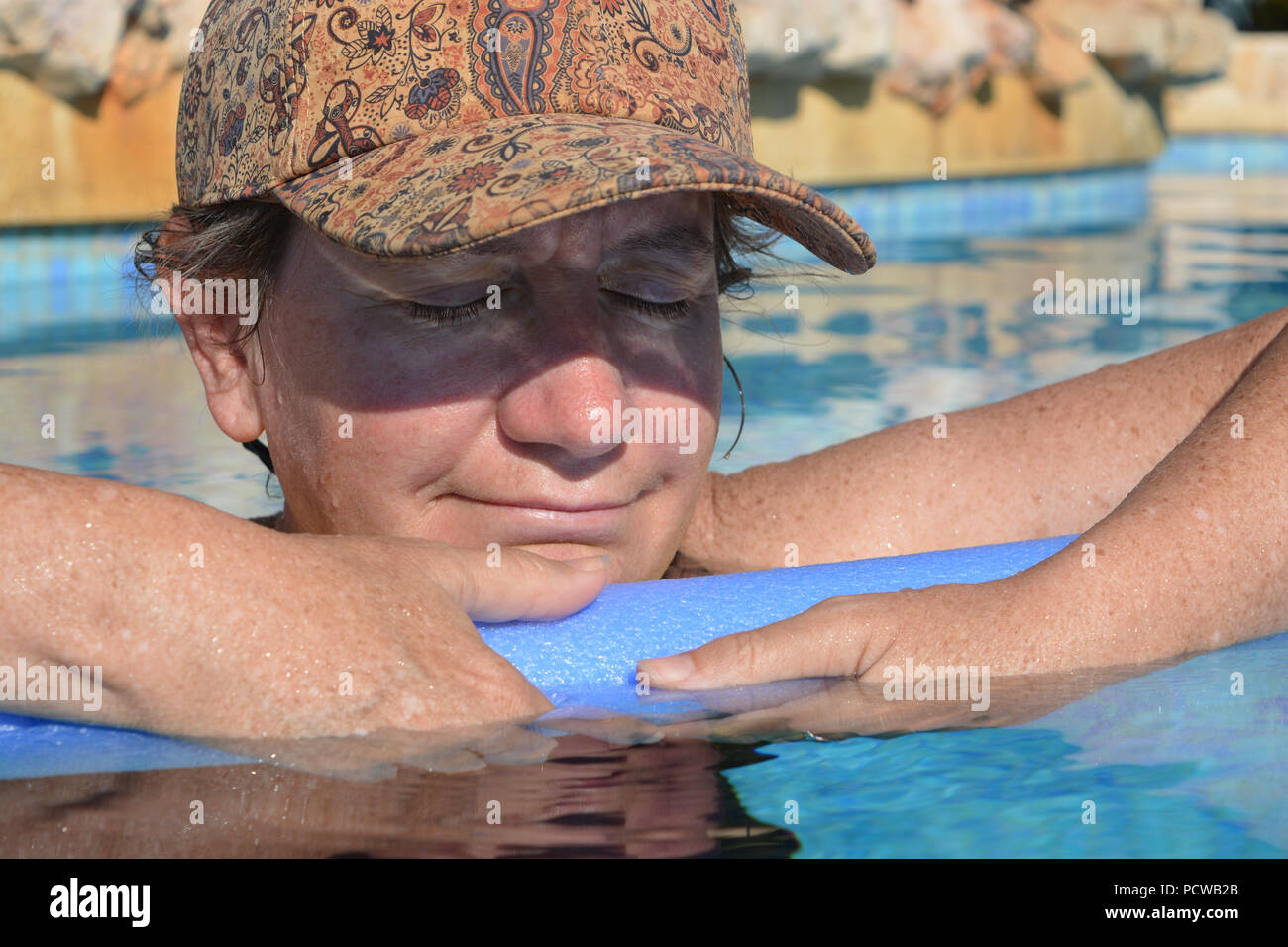 Woman, holding a pool noodle floating in a swimming pool, relaxed, eyes closed - Stock Image