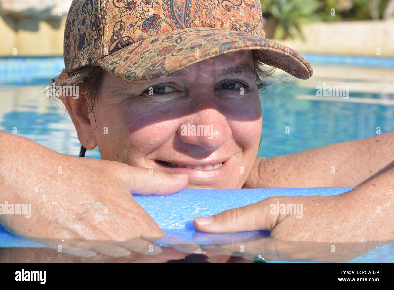 Woman, holding a pool noodle floating in a swimming pool, smiling to camera - Stock Image