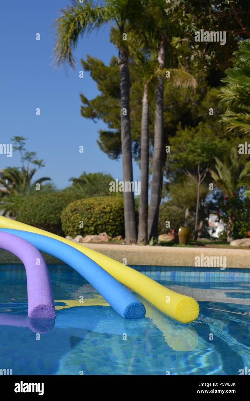 Three pool noodles at the poolside in a private garden, Spain - Stock Image