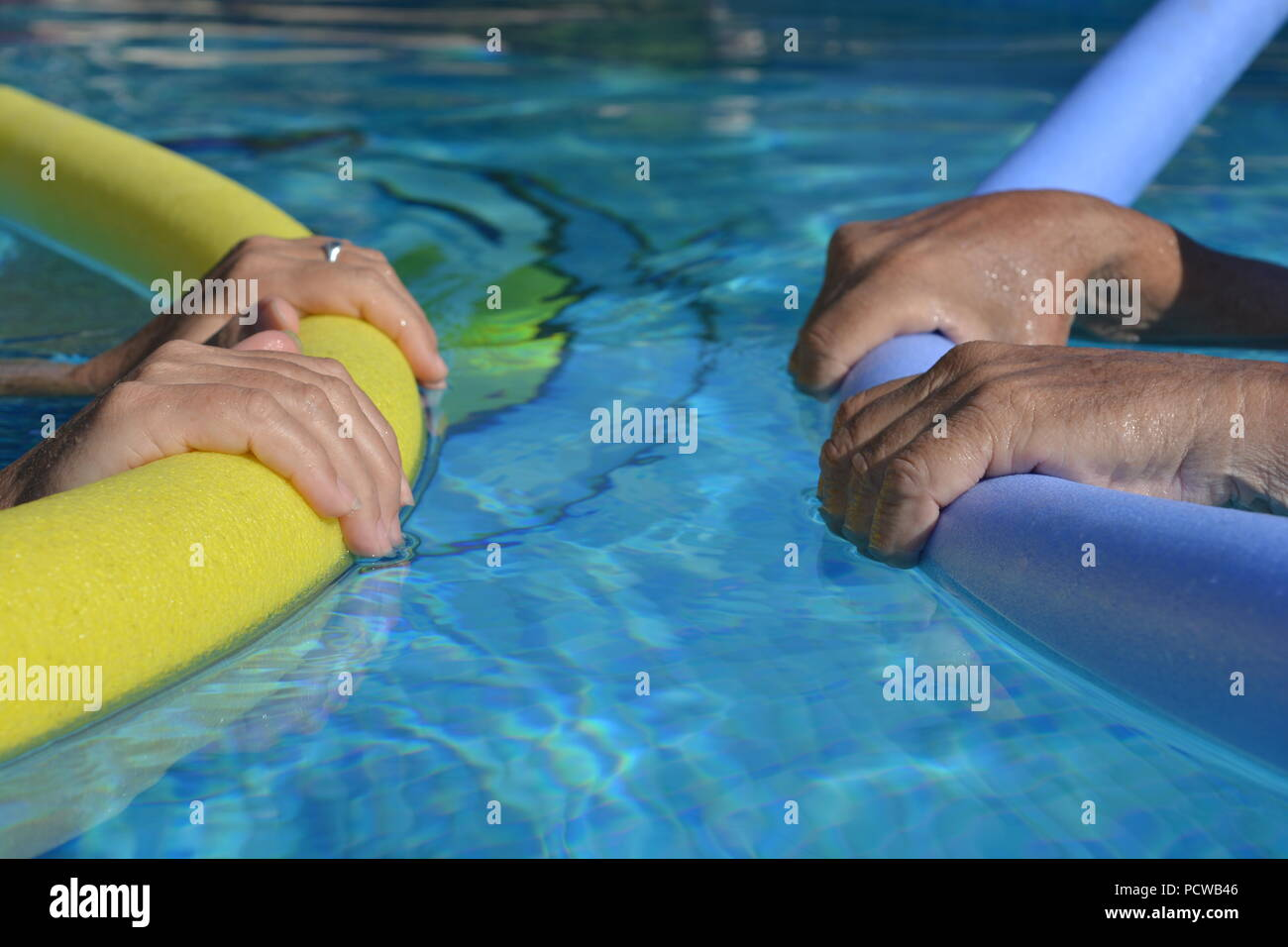 Couple in swimming pool, facing each other, floating with pool noodles, selective focus on hands holding the noodles - Stock Image