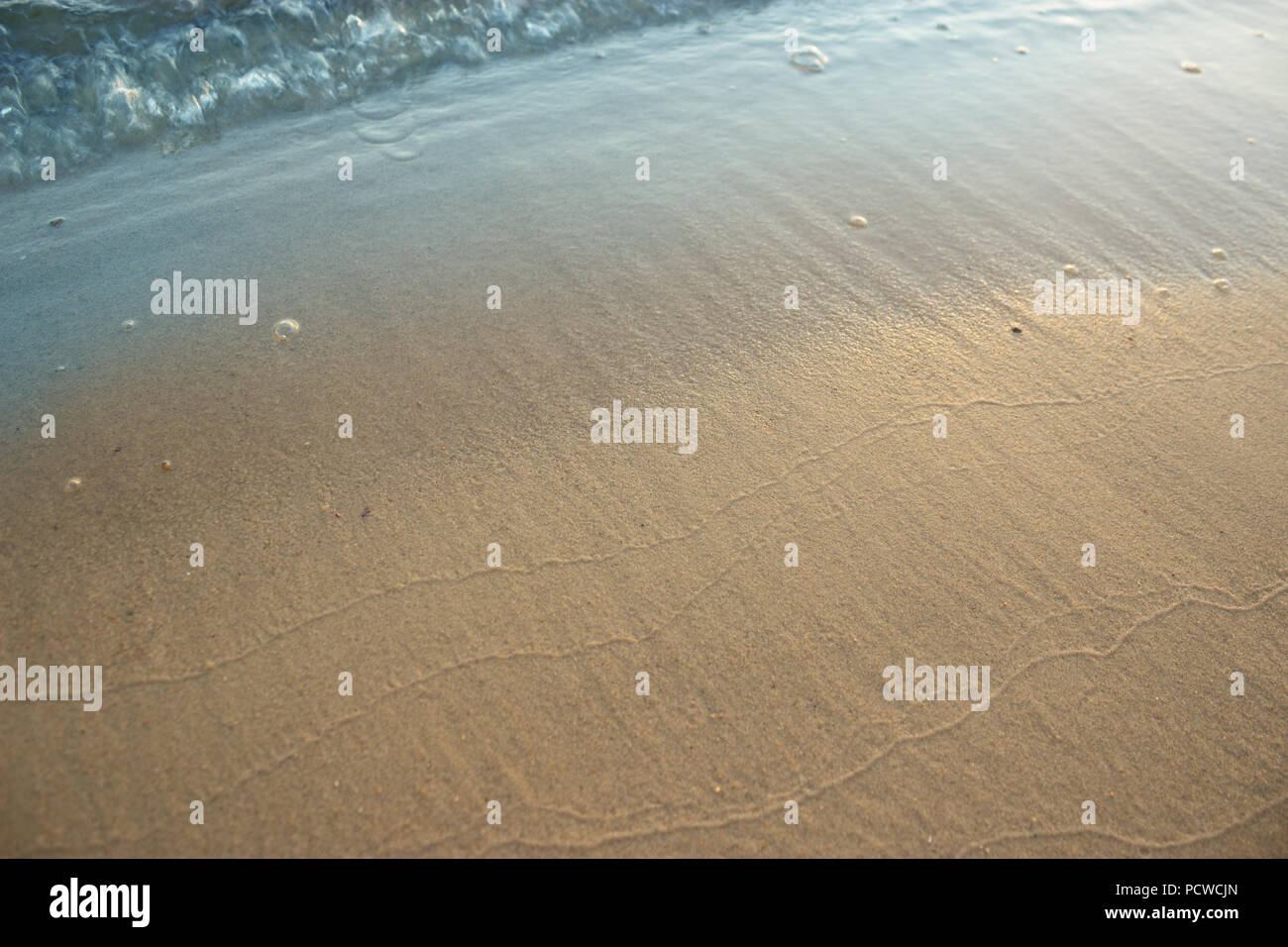 Sunset and Gentle Surf. waves sand and copy space - Stock Image