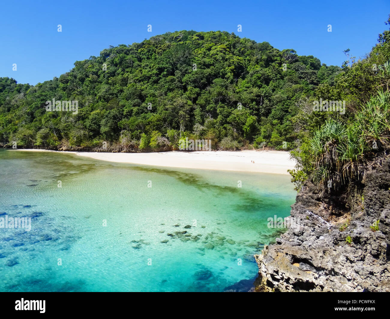 People relax on desert white sand beach after trekking in tropical jungle to Segara Anakan lagoon with clear water. Scenic view of hidden natural pool - Stock Image