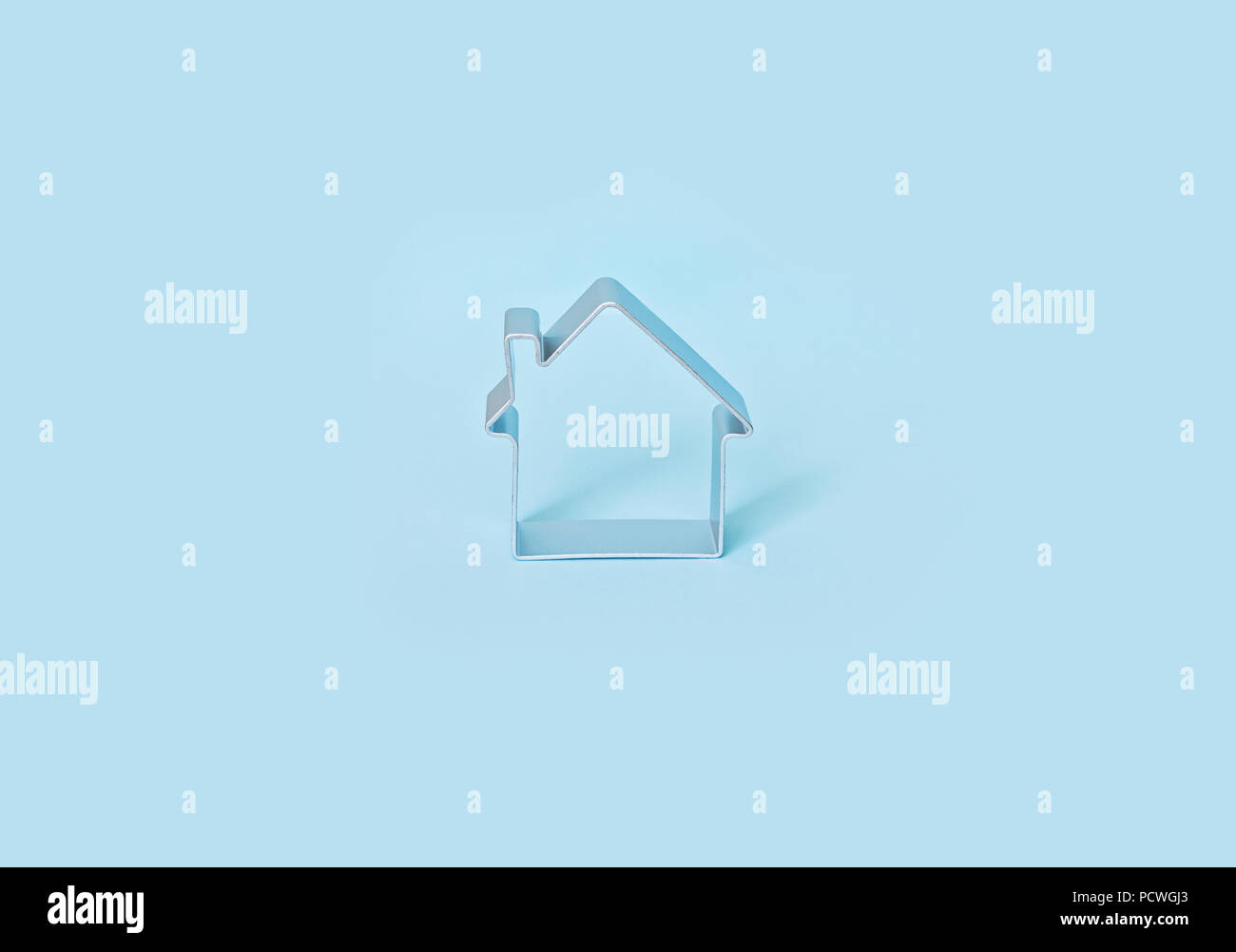 Simple shape of small house isolated on blue background. Insurance and rental housing concept Stock Photo