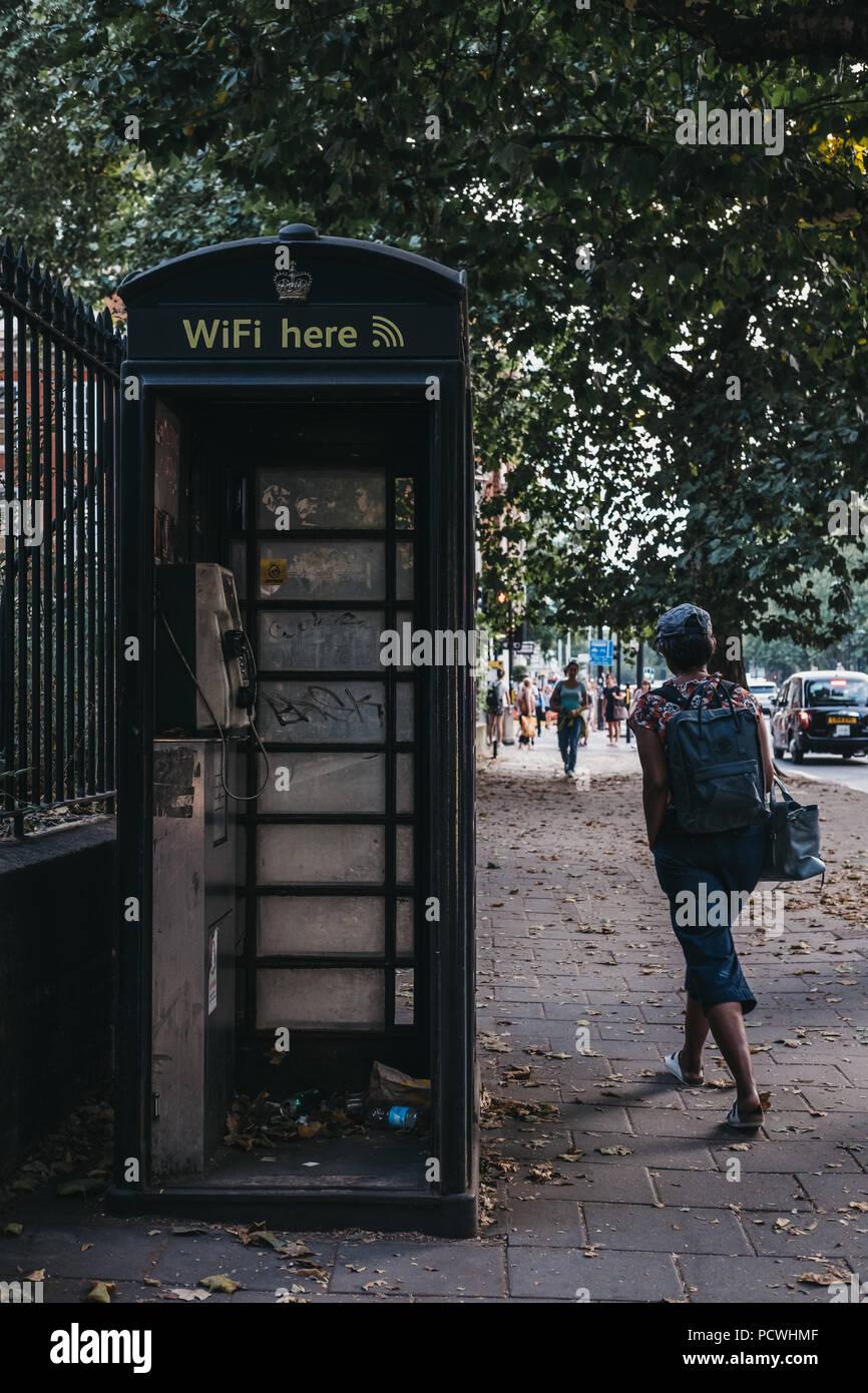 Woman walks past black phone box on Euston Road in London, UK. - Stock Image