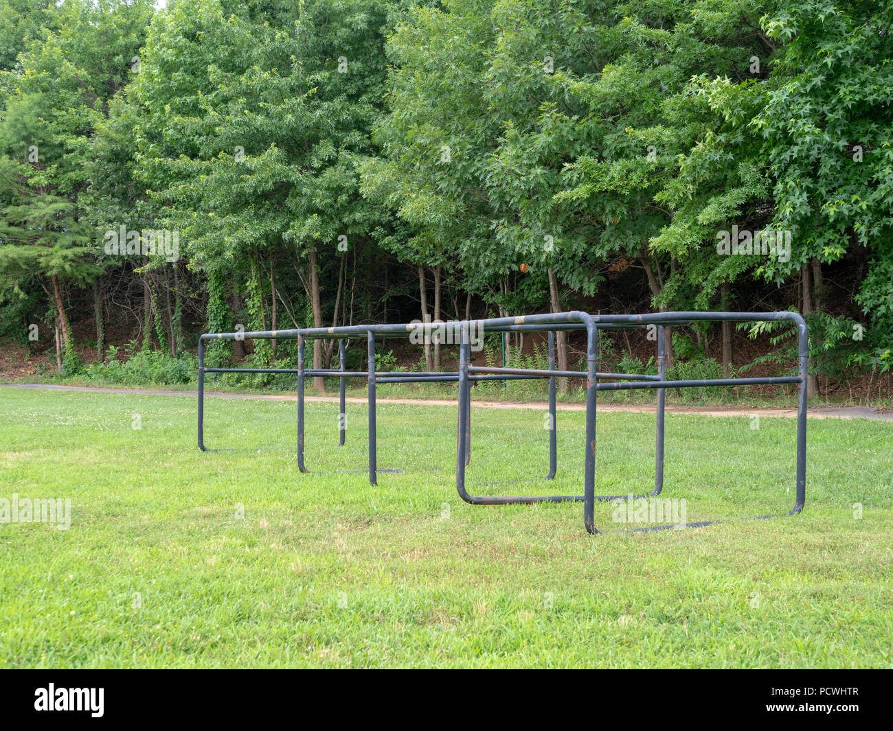 Old, damaged football chutes sitting in a grassy field in the offseason - Stock Image