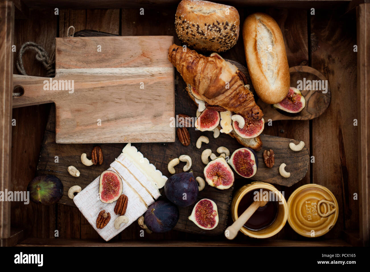breakfast. a croissant with figs and honey. brie cheese and nuts. wooden board. Vintage background. brown photo. family breakfast. homemade baking - Stock Image