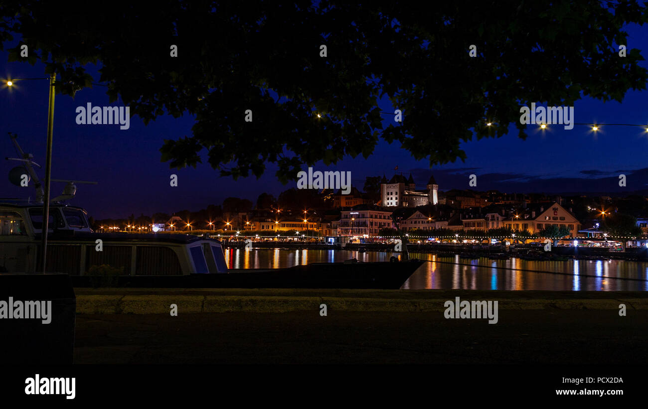 Skyline of Nyon by night with a boat docked to a pier - Stock Image