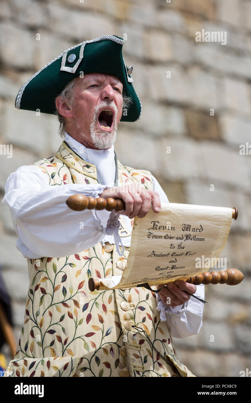 Windsor, UK. 4th August, 2018. Kevin Ward, Town Crier of Bromsgrove, takes part in the Ancient and Honourable Guild of Town Criers (AHGTC) National Championship beneath the walls of Windsor Castle. Forty town criers from across the UK and two from Australia compete in two rounds of crying, the first a home cry scored on diction, inflection, clarity and volume and the second a cry on the topic of 'A Celebration'. Credit: Mark Kerrison/Alamy Live News - Stock Image