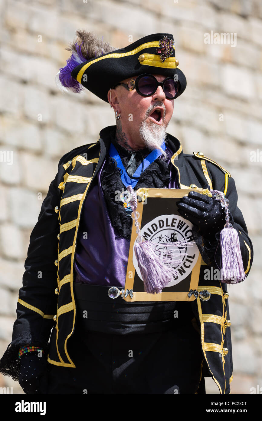 Windsor, UK. 4th August, 2018. Devlin Hobson, Town Crier of Middlewich, takes part in the Ancient and Honourable Guild of Town Criers (AHGTC) National Championship beneath the walls of Windsor Castle. Forty town criers from across the UK and two from Australia compete in two rounds of crying, the first a home cry scored on diction, inflection, clarity and volume and the second a cry on the topic of 'A Celebration'. Credit: Mark Kerrison/Alamy Live News - Stock Image