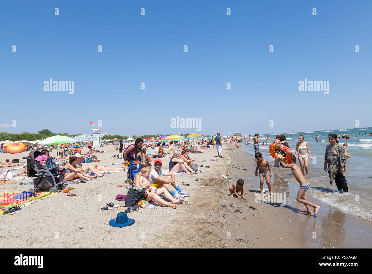 Lido, Venice, Italy, 4th August 2018. People escape the heatwave currently gripping Europe by spending their Saturday afternoon on Blue Moon beach, Lido di Venezia, Venice, Italy. The temperature in Venice has been in the mid to high thirties all week and is set to continue into next week.  Credit Mary Clarke/Alamy Live News - Stock Image