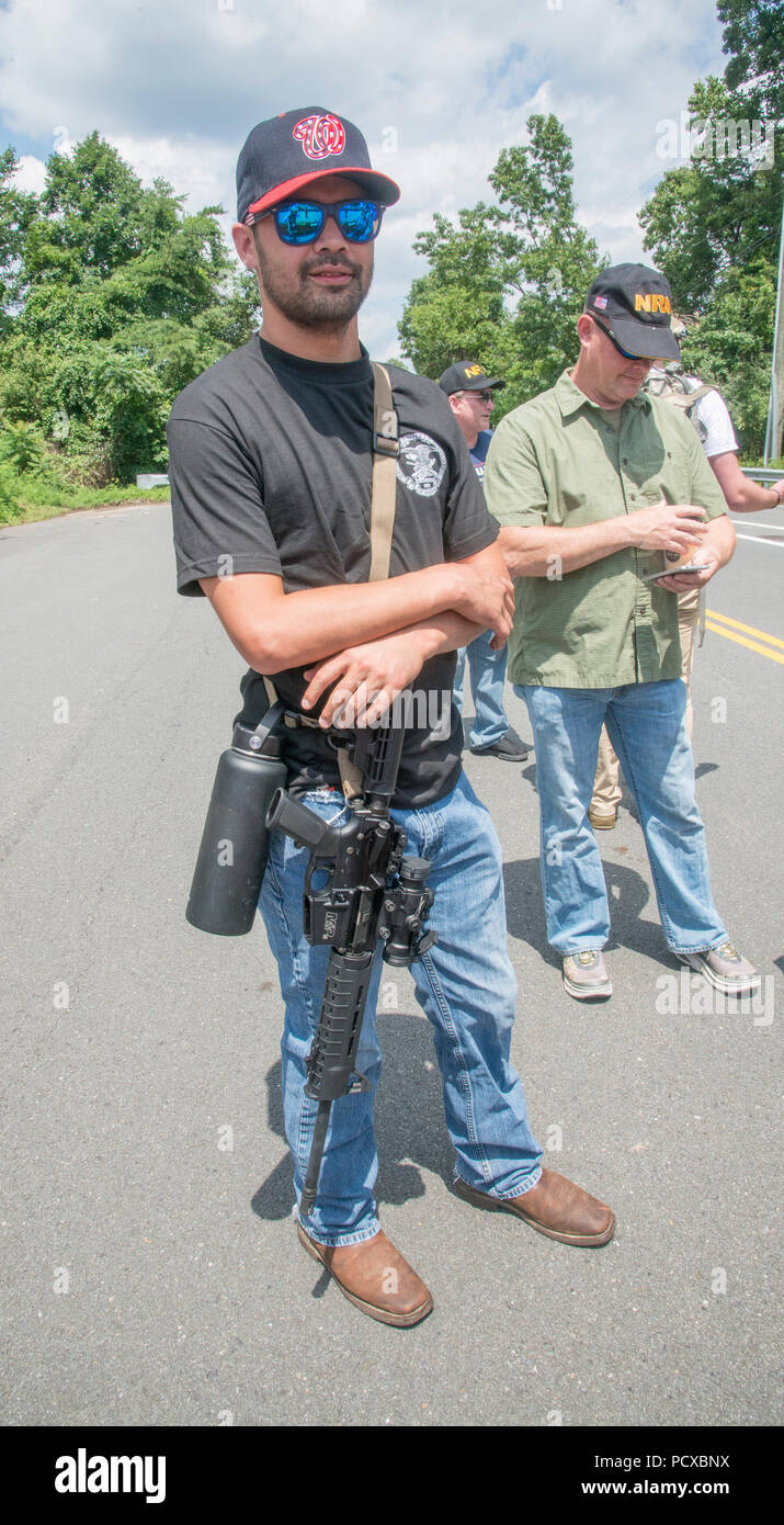 "Fairfax,VA August 4 2018, USA: A pro gun supporters carries his unarrmed assualt style gun as  demonstrators on both sides of the gun control issue rally at the National headquarters of the National Rifle Association (NRA) in Fairfax, VA.  Dubbed  ""The March on the NRA"" protestors line the streets in fron the of headquarters.  DC.  Patsy Lynch/Alamy Stock Photo"